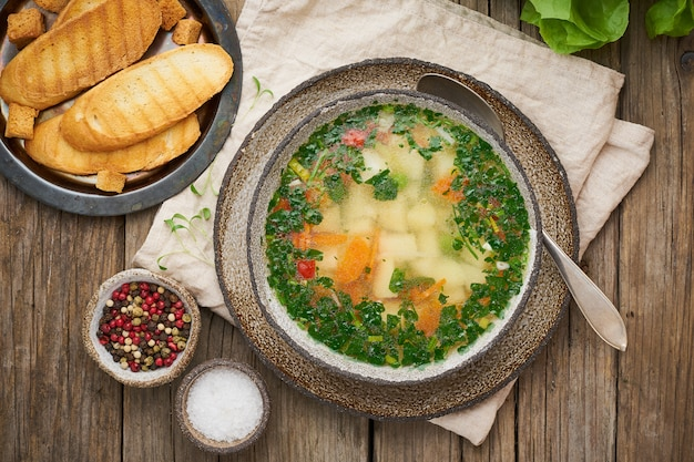 Rustic chicken soup with garnish, parsley, vegetables, homemade dish on old dark table, top view