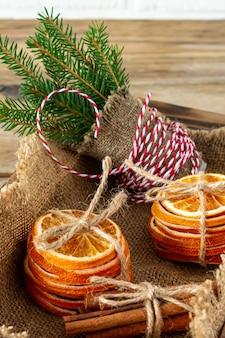 Деревенская рождественская композиция с сушеными апельсинами, палочками корицы и еловыми ветками в деревянном ящике.