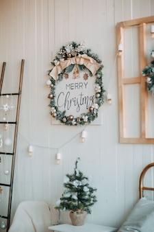 소박한 크리스마스 장식. 램프와 크리스마스 화 환 흰색 나무 벽.