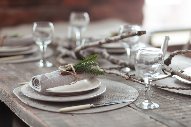 Rustic christmas served wooden table with vintage silverware, candles and fir twigs.