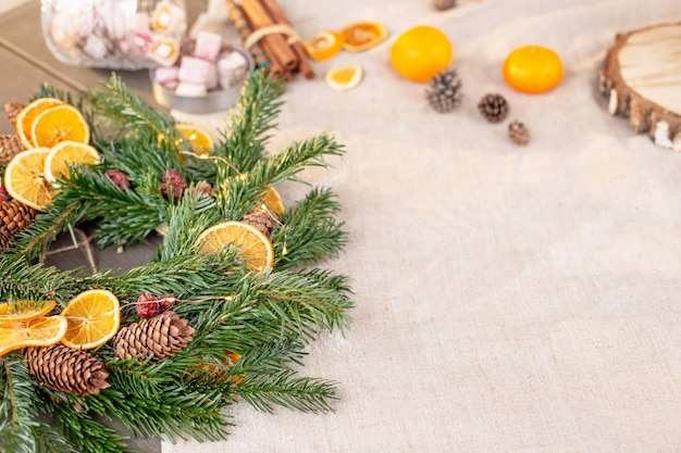 自然なトウヒの花輪乾燥オレンジ松ぼっくりタンジェリンと素朴なクリスマステーブルの装飾