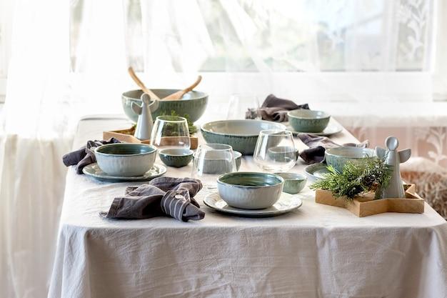 空のクラフトセラミック食器、プレートとボウル、クリスマスの天使の装飾、ガラス、白いテーブルクロスの上の緑の枝と素朴なクリスマステーブルの設定