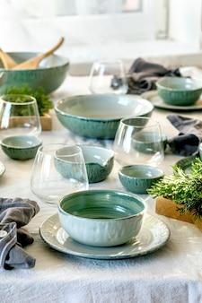 Деревенская рождественская сервировка стола с пустой керамической посудой, тарелками и мисками, рождественскими украшениями ангела, очками, зелеными ветками на белой скатерти