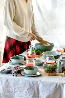 空のクラフトセラミック食器、プレートとボウル、窓の前の白いテーブルクロスにクリスマスの天使の装飾が施された素朴なクリスマステーブルの設定。女性はサラダボウルを保持します