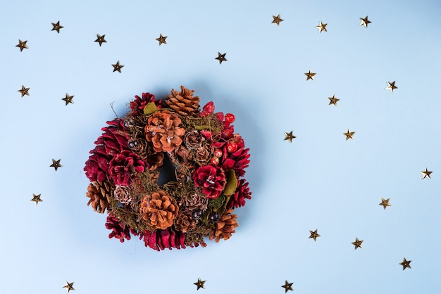 Rustic christmas wreath with decorations on stars blue paper backround, flat lay