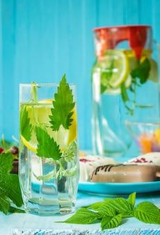 青いプレート上の木製のテーブルアイスクリームの素朴なコンセプトの朝食レモンと水のガラス