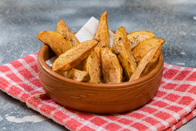 Rustic or countrie style fried potatoes with herbs in a ceramic bowl on a concrete surface