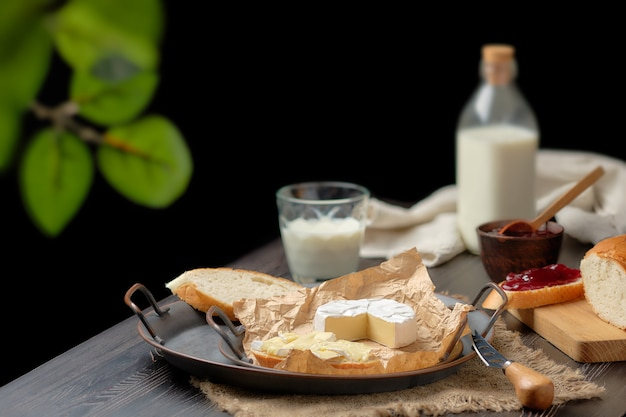 Rustic country breakfast with brie cheese, milk, baguette and cranberry jam