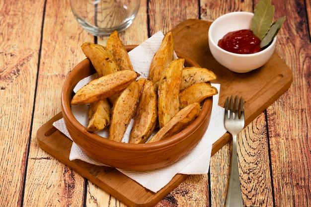 Rustic or country style fries potatoes with herbs in a ceramic bowl on a wooden board with barbecue sauce with herbs on wooden table
