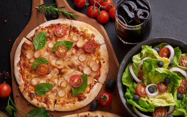 Rustic dark stone table with various kinds of italian pizza, top view. fast food lunch, celebration