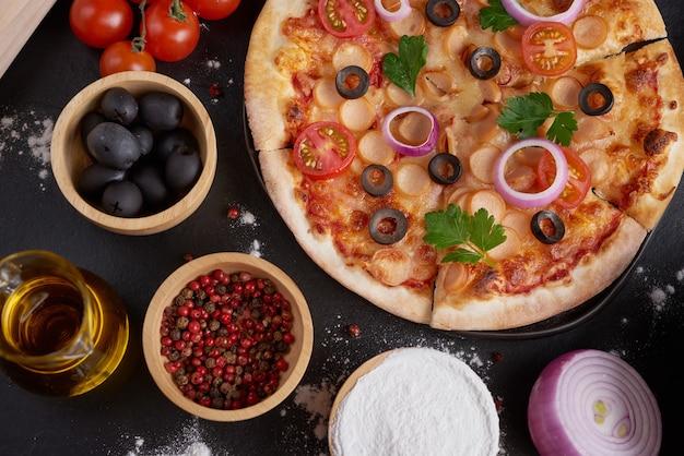 さまざまな種類のイタリアンピザを備えた素朴なダークストーンのテーブル、上面図。ファーストフードランチ、お祝い