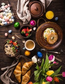 素朴なイースターの朝食フラットは、卵のベーグル、チューリップ、クロワッサン、卵、ベリーのオートミール、色付きのウズラの卵、春の休日の装飾で横たわっていました。上面図