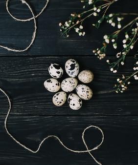 메추라기 계란과 어두운 나무 배경에 버드 나무 가지와 소박한 부활절 정물화