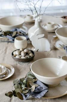 빈 공예 세라믹 식기, 접시와 그릇, 부활절 토끼 장식, 창 앞의 리넨 식탁보에 꽃병에 가지와 소박한 부활절 테이블 설정입니다. 부활절 휴일 저녁.