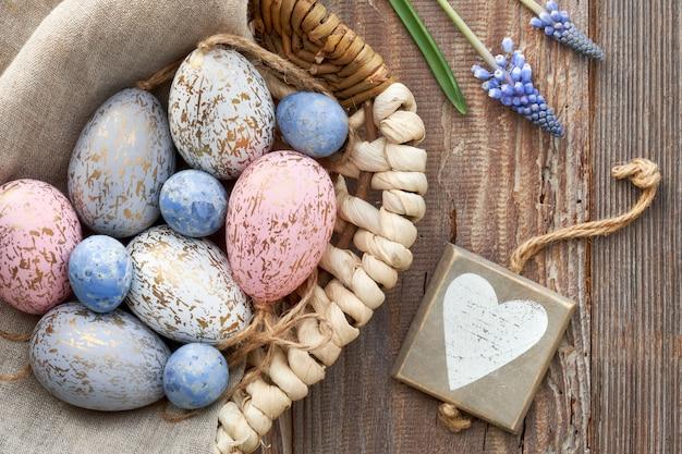 卵、青いヒヤシンスの花、木の心、トップビューで素朴なイースター壁