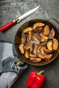 Rustic food. fried potatoes in a pan on a dark concrete table. rustic style.
