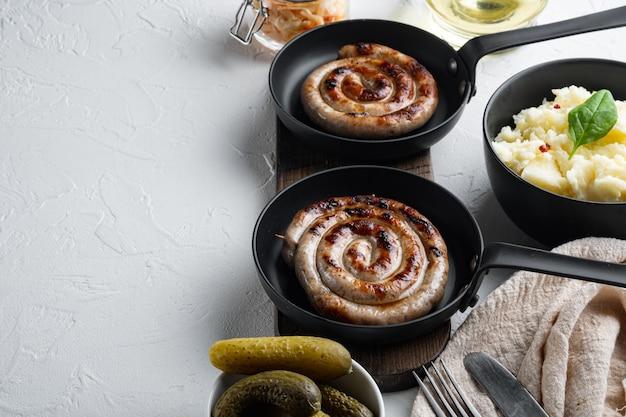 Деревенская еда с жареной колбасой, картофельным пюре и квашеной капустой в чугунной сковороде, на белом фоне,