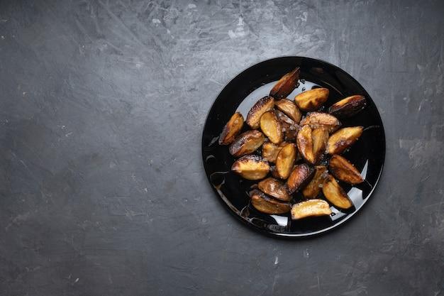 テーブルの上の黒い皿に素朴なフライドポテト、上面図