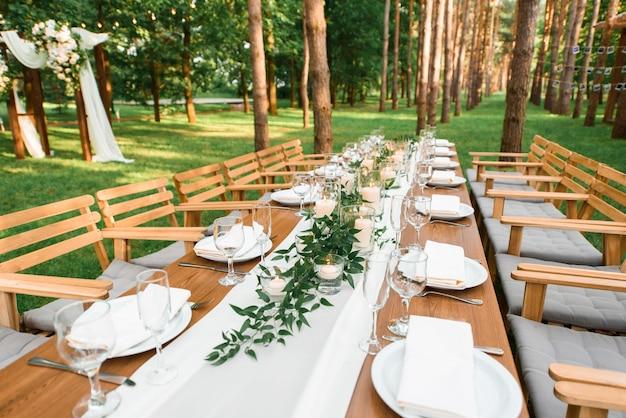 Деревенская зеленая ветка и свечи на столе. свадебные украшения.