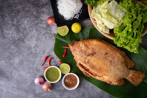 Rustic grilled fish on kitchen table, traditional thai food.