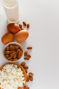 Rustic homemade protein balanced diet food cottage cheese eggs nuts and milk on white background