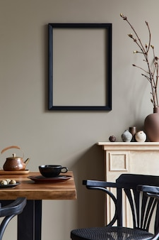 Rustic interior design of dining room with wooden family table, candelstick, retro chair, cup of coffee, decoration, picture frame and elegant personal accessories. beige wall..