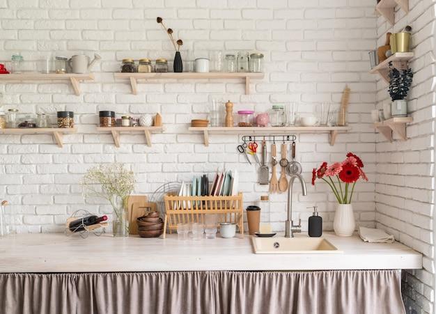 Деревенский интерьер кухни с белой кирпичной стеной и белыми деревянными полками. свежие цветы герберы