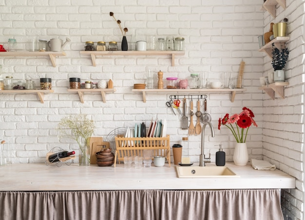 Rustic kitchen interior with white brick wall and white wooden shelves. fresh gerbera flowers