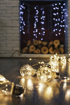 Rustic light bulb garden lights at home, fireplace background selected focus