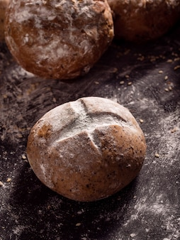 The rustic loaves of bread placed on wooden black background
