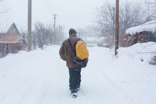 A rustic man is walking down the street in winter with a yellow backpack. snow blizzard