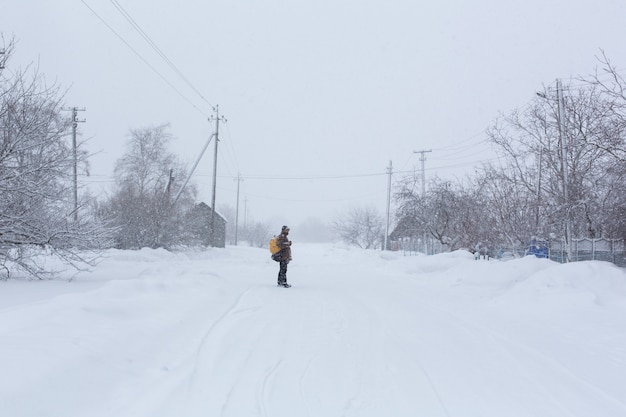 A rustic man is walking down the street in winter with a yellow backpack. snow blizzard.
