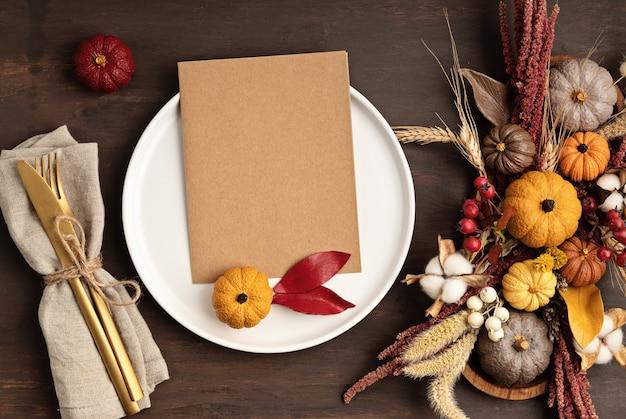 Макет меню в деревенском стиле с тарелкой и украшением осеннего стола. цветочный декор интерьера для осенних праздников с помощью тыкв ручной работы. концепция праздничного ужина. flatlay, вид сверху