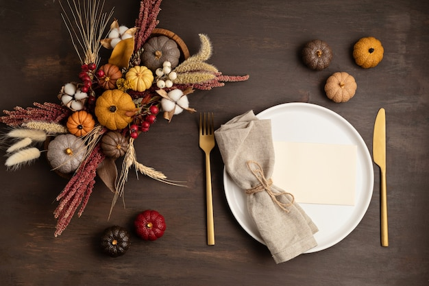 Rustic menu mockup with plate and autumn table decoration. floral interior decor for fall holidays with handmade pumpkins. holiday dinner concept. flatlay, top view