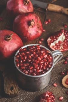 석류 씨앗이 가득한 소박한 금속 머그입니다. 어두운 나무 테이블에 전체 과일과 석류 조각.