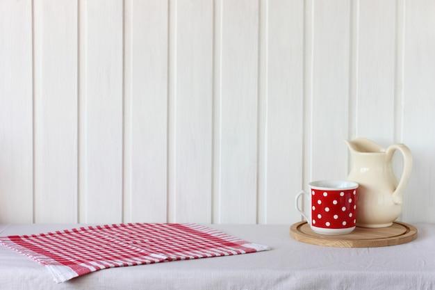 Деревенский макет с полотенцем и посудой на столе. красный и белый фон. пустое место для вашего объекта.