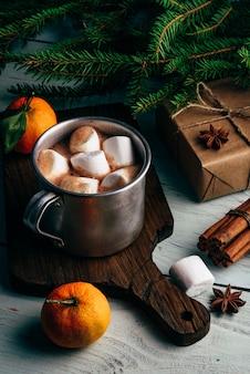 마시멜로와 핫 초콜릿의 소박한 머그입니다. 나무 테이블에 크리스마스 선물과 귤