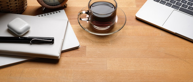 Rustic office desk with coffee cup, laptop, schedule books, pen and decorations on wooden table