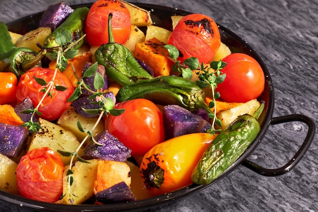 Rustic oven baked vegetables in black baking dish con gray stone background. seasonal vegetarian vegan meal