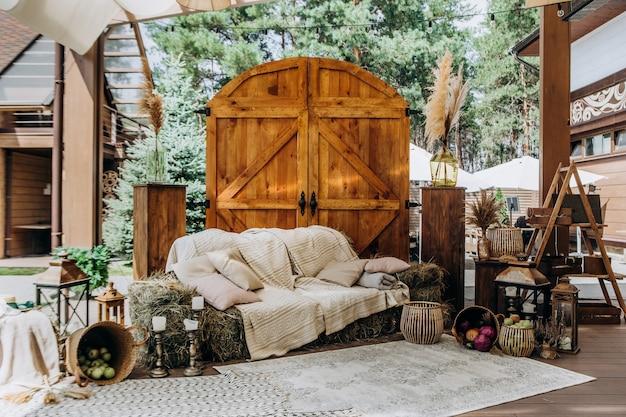 素朴な写真ゾーンの装飾干し草ソファ木製ゲートバスケット野菜とキャンドル