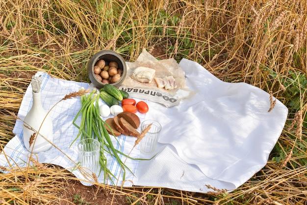 Деревенский пикник с огурцом, картофелем, помидорами и беконом с бутылкой самогона в поле с сельскохозяйственными культурами. пшеничное поле.