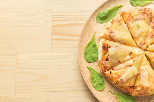 木製の背景に素朴なピザ。上面図
