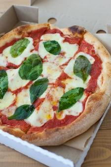 サラミ、モッツァレラチーズ、オリーブ、バジルのトップビューとコピースペースの素朴なピザ。