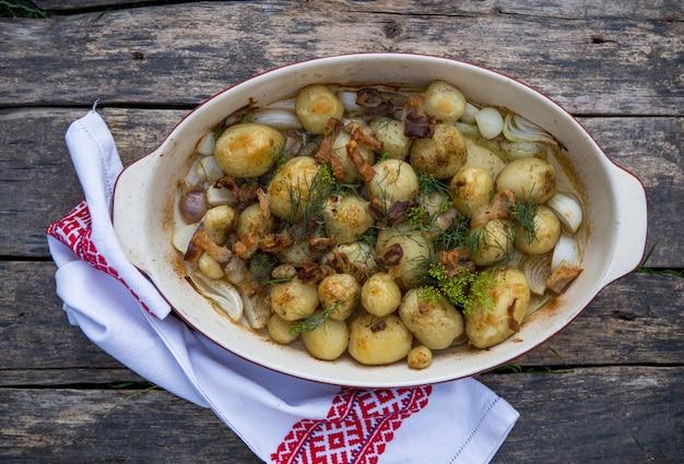 냄비에 소박한 감자입니다. 마늘과 허브 껍질에 구운 작은 감자.