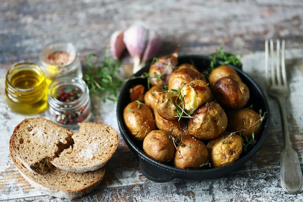 Rustic potato in a pan. baked small potatoes in a peel with garlic and herbs. selective focus.