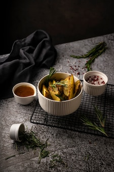 Rustic potatoes cut into slices with rosemary in a white dish with butter and spices on a dark background