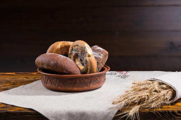 小麦の耳と暗い木の背景のコピースペースと古い木製のテーブルの上の各種ロールパンとベーグルの素朴な陶器ボウル