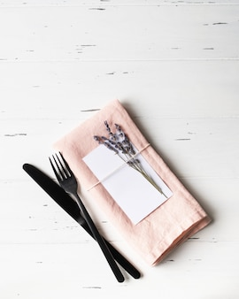 Rustic romantic table setting with paper card, pink napkin, lavender and appliances on white wood table. top view. copy space