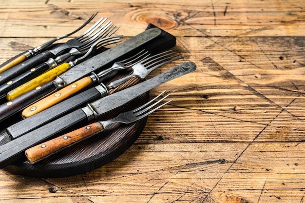カトラリーナイフとフォークの素朴なセット。木製の背景。上面図。スペースをコピーします。