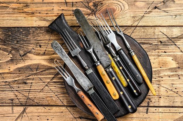 カトラリーナイフとフォークの素朴なセット。木製の背景。上面図。